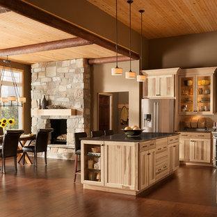 Modelo de cocina en L, rústica, abierta, con fregadero bajoencimera, armarios con rebordes decorativos, puertas de armario de madera clara, encimera de cuarzo compacto, salpicadero blanco, salpicadero de azulejos de piedra y electrodomésticos de acero inoxidable