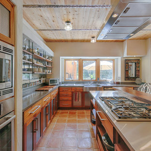 Rustic kitchen designs - Inspiration for a rustic l-shaped orange floor kitchen remodel in San Francisco with a farmhouse sink, medium tone wood cabinets, stainless steel appliances and an island