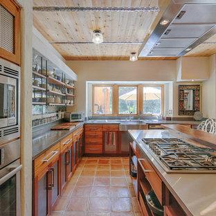 Foto de cocina en L, rústica, con fregadero sobremueble, puertas de armario de madera oscura, electrodomésticos de acero inoxidable, una isla y suelo naranja