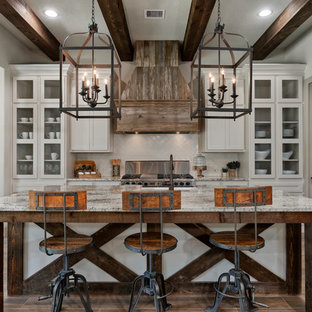 Mountain style l-shaped brown floor enclosed kitchen photo in Houston with a farmhouse sink, granite countertops, white backsplash, ceramic backsplash, stainless steel appliances, an island, glass-front cabinets, white cabinets and multicolored countertops