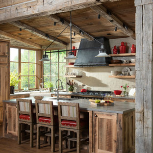 Rustic kitchen ideas - Example of a mountain style l-shaped medium tone wood floor kitchen design in Other with a farmhouse sink, shaker cabinets, distressed cabinets, beige backsplash, subway tile backsplash, an island and gray countertops
