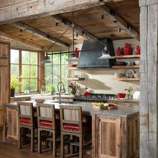 他の地域のラスティックスタイルのおしゃれなキッチン (エプロンフロントシンク、シェーカースタイル扉のキャビネット、ヴィンテージ仕上げキャビネット、ベージュキッチンパネル、サブウェイタイルのキッチンパネル、無垢フローリング、グレーのキッチンカウンター) の写真