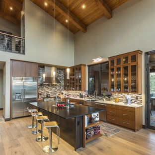 Rustic kitchen designs - Inspiration for a rustic l-shaped light wood floor kitchen remodel in Philadelphia with a farmhouse sink, glass-front cabinets, medium tone wood cabinets, multicolored backsplash, matchstick tile backsplash, stainless steel appliances, an island and beige countertops
