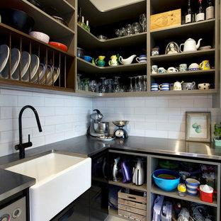 Stilmix Küche in L-Form mit Vorratsschrank, Landhausspüle, flächenbündigen Schrankfronten, hellbraunen Holzschränken, Edelstahl-Arbeitsplatte, Küchenrückwand in Weiß, Rückwand aus Metrofliesen, Küchengeräten aus Edelstahl und Kücheninsel in Auckland