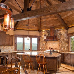 デンバーの巨大なラスティックスタイルのおしゃれなキッチン (アンダーカウンターシンク、シェーカースタイル扉のキャビネット、濃色木目調キャビネット、御影石カウンター、マルチカラーのキッチンパネル、石タイルのキッチンパネル、シルバーの調理設備、トラバーチンの床、ベージュの床) の写真