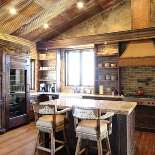 Mid-sized country u-shaped eat-in kitchen in Austin with a farmhouse sink, louvered cabinets, distressed cabinets, granite benchtops, multi-coloured splashback, stone tile splashback, panelled appliances, medium hardwood floors and with island.