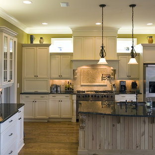 This is an example of a country galley kitchen in Charlotte with recessed-panel cabinets, stainless steel appliances, an undermount sink, beige cabinets and beige splashback.