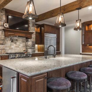 デトロイトの巨大なラスティックスタイルのおしゃれなキッチン (アンダーカウンターシンク、レイズドパネル扉のキャビネット、中間色木目調キャビネット、クオーツストーンカウンター、ベージュキッチンパネル、石タイルのキッチンパネル、シルバーの調理設備の、スレートの床、緑の床) の写真