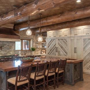 ソルトレイクシティのラスティックスタイルのおしゃれなアイランドキッチン (シェーカースタイル扉のキャビネット、淡色木目調キャビネット、マルチカラーのキッチンパネル、ボーダータイルのキッチンパネル、濃色無垢フローリング、茶色い床、ベージュのキッチンカウンター) の写真