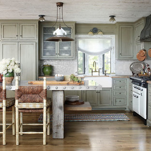 Photo of a country l-shaped kitchen in Milwaukee with shaker cabinets, green cabinets, grey splashback and white appliances.