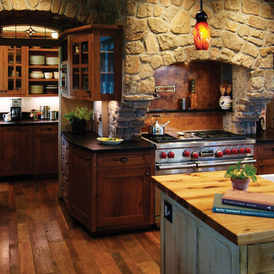 Mountain style dark wood floor kitchen photo in Denver with dark wood cabinets, brown backsplash, stainless steel appliances, a drop-in sink, recessed-panel cabinets, wood countertops, stone slab backsplash and an island