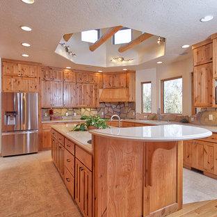 他の地域の大きいラスティックスタイルのおしゃれなキッチン (ダブルシンク、シェーカースタイル扉のキャビネット、中間色木目調キャビネット、クオーツストーンカウンター、ベージュキッチンパネル、石タイルのキッチンパネル、シルバーの調理設備の、リノリウムの床) の写真