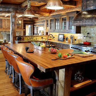 Idéer för ett rustikt kök, med luckor med glaspanel, träbänkskiva, skåp i mörkt trä och gult stänkskydd