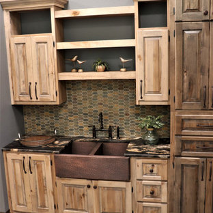 Photo of a mid-sized country single-wall kitchen in Other with a double-bowl sink, raised-panel cabinets, granite benchtops, multi-coloured splashback, slate splashback, porcelain floors, brown floor, black benchtop and light wood cabinets.