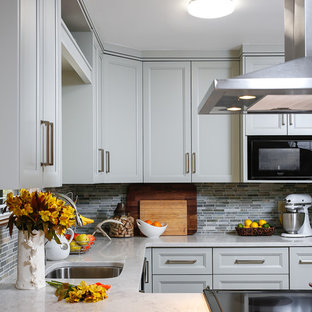 Small country u-shaped eat-in kitchen in Miami with an undermount sink, raised-panel cabinets, green cabinets, quartz benchtops, green splashback, stone tile splashback, black appliances, ceramic floors and a peninsula.