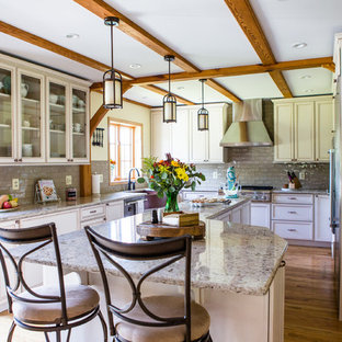 This is an example of a traditional u-shaped kitchen in Baltimore with a farmhouse sink, recessed-panel cabinets, beige cabinets, grey splashback, stainless steel appliances, medium hardwood floors and with island.