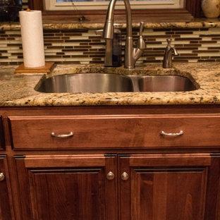 他の地域の中くらいのトランジショナルスタイルのおしゃれなキッチン (アンダーカウンターシンク、レイズドパネル扉のキャビネット、濃色木目調キャビネット、御影石カウンター、マルチカラーのキッチンパネル、ボーダータイルのキッチンパネル、シルバーの調理設備、テラコッタタイルの床、赤い床、ベージュのキッチンカウンター) の写真
