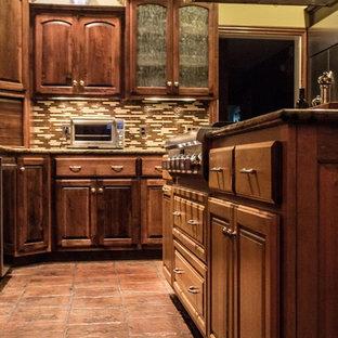 他の地域の中サイズのトランジショナルスタイルのおしゃれなキッチン (アンダーカウンターシンク、レイズドパネル扉のキャビネット、濃色木目調キャビネット、御影石カウンター、マルチカラーのキッチンパネル、ボーダータイルのキッチンパネル、シルバーの調理設備の、テラコッタタイルの床、赤い床、ベージュのキッチンカウンター) の写真