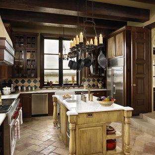 Ejemplo de cocina rústica con puertas de armario de madera en tonos medios, salpicadero multicolor y electrodomésticos de acero inoxidable