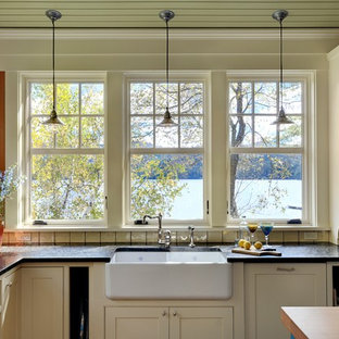 Rustic kitchen designs - Inspiration for a rustic kitchen remodel in Burlington with a farmhouse sink, beaded inset cabinets and beige cabinets