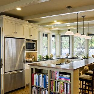Urige Küche in L-Form mit Schrankfronten im Shaker-Stil, Küchengeräten aus Edelstahl, Arbeitsplatte aus Holz und beigen Schränken in Burlington