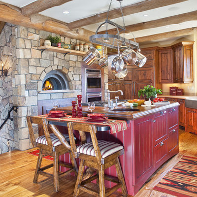 Mid-sized mountain style u-shaped light wood floor kitchen photo in Denver with a farmhouse sink, red cabinets, raised-panel cabinets, wood countertops and an island
