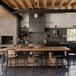 Rustikale Wohnküche mit Landhausspüle, Arbeitsplatte aus Holz, Küchengeräten aus Edelstahl, Betonboden, offenen Schränken, hellen Holzschränken, Küchenrückwand in Grau, Kücheninsel, schwarzem Boden und brauner Arbeitsplatte in Sonstige