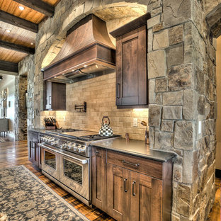 Huge rustic eat-in kitchen remodeling - Example of a huge mountain style l-shaped medium tone wood floor eat-in kitchen design in Denver with an undermount sink, shaker cabinets, medium tone wood cabinets, granite countertops, beige backsplash, stone tile backsplash, stainless steel appliances and two islands