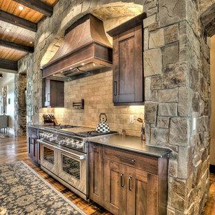 デンバーの巨大なラスティックスタイルのおしゃれなキッチン (アンダーカウンターシンク、シェーカースタイル扉のキャビネット、中間色木目調キャビネット、御影石カウンター、ベージュキッチンパネル、石タイルのキッチンパネル、シルバーの調理設備の、無垢フローリング) の写真