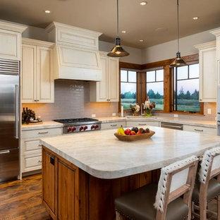 他の地域の広いラスティックスタイルのおしゃれなキッチン (アンダーカウンターシンク、レイズドパネル扉のキャビネット、ベージュのキャビネット、グレーのキッチンパネル、シルバーの調理設備、ベージュのキッチンカウンター、サブウェイタイルのキッチンパネル、濃色無垢フローリング、茶色い床) の写真