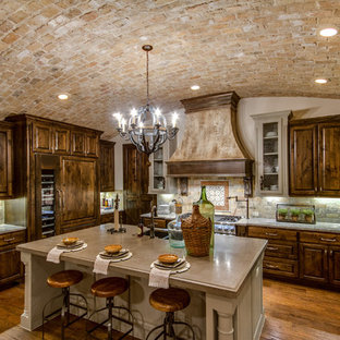 This is an example of a large mediterranean u-shaped open plan kitchen in Austin with a double-bowl sink, flat-panel cabinets, medium wood cabinets, limestone benchtops, mosaic tile splashback, medium hardwood floors and with island.