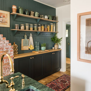This is an example of a mid-sized country galley separate kitchen in Vancouver with an undermount sink, shaker cabinets, black cabinets, granite benchtops, green splashback, stainless steel appliances, light hardwood floors, with island, brown floor and green benchtop.