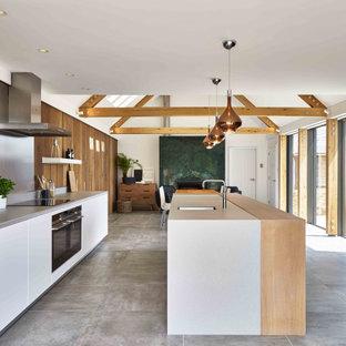 デヴォンの中サイズのエクレクティックスタイルのおしゃれなキッチン (一体型シンク、フラットパネル扉のキャビネット、白いキャビネット、人工大理石カウンター、マルチカラーのキッチンパネル、メタルタイルのキッチンパネル、黒い調理設備、セラミックタイルの床、グレーの床、グレーのキッチンカウンター) の写真