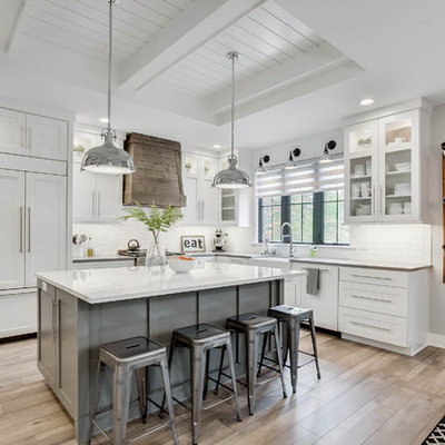 Farmhouse l-shaped brown floor eat-in kitchen photo in Grand Rapids with a farmhouse sink, shaker cabinets, white cabinets, white backsplash, subway tile backsplash, paneled appliances, an island and white countertops