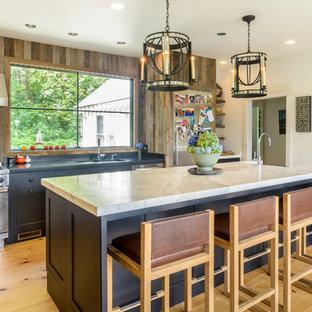 ボストンのカントリー風おしゃれなアイランドキッチン (エプロンフロントシンク、落し込みパネル扉のキャビネット、グレーのキャビネット、大理石カウンター、シルバーの調理設備の、無垢フローリング、茶色いキッチンパネル) の写真