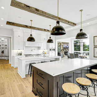 Design ideas for a transitional l-shaped kitchen in Minneapolis with an undermount sink, shaker cabinets, white cabinets, white splashback, panelled appliances, medium hardwood floors, multiple islands, brown floor and white benchtop.