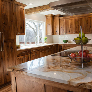 Photo of a medium sized rustic l-shaped kitchen/diner in Indianapolis with medium wood cabinets, quartz worktops, white splashback, metro tiled splashback, integrated appliances, light hardwood flooring, an island, a submerged sink, shaker cabinets and multicoloured worktops.