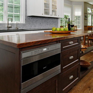 Inspiration for a rustic u-shaped medium tone wood floor eat-in kitchen remodel in DC Metro with an undermount sink, shaker cabinets, white cabinets, quartz countertops, multicolored backsplash, stone tile backsplash, stainless steel appliances and an island