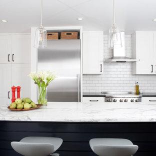 サンフランシスコのミッドセンチュリースタイルのおしゃれな独立型キッチン (サブウェイタイルのキッチンパネル、シルバーの調理設備、シェーカースタイル扉のキャビネット、白いキャビネット、大理石カウンター、白いキッチンパネル) の写真