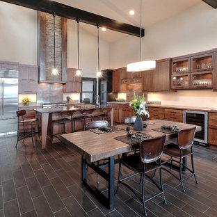 Ejemplo de cocina comedor en L, rústica, grande, con armarios con paneles lisos, puertas de armario de madera oscura, electrodomésticos de acero inoxidable, una isla y suelo de baldosas de porcelana