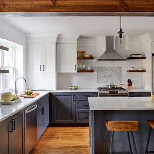 Transitional kitchen designs - Inspiration for a transitional l-shaped medium tone wood floor kitchen remodel in Chicago with an undermount sink, shaker cabinets, blue cabinets, white backsplash, subway tile backsplash, stainless steel appliances, an island and white countertops