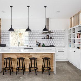 Mittelgroße, Offene Skandinavische Küche mit flächenbündigen Schrankfronten, weißen Schränken, Küchenrückwand in Weiß, Rückwand aus Keramikfliesen, Küchengeräten aus Edelstahl, Betonboden, Kücheninsel, grauem Boden und weißer Arbeitsplatte in Austin