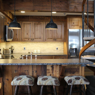 Inspiration for a rustic u-shaped kitchen pantry in Boston with a belfast sink, beaded cabinets, medium wood cabinets, granite worktops, beige splashback, stone tiled splashback, stainless steel appliances, porcelain flooring, no island, brown floors and multicoloured worktops.
