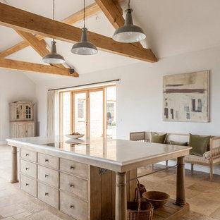 グロスタシャーの大きいラスティックスタイルのおしゃれなキッチン (シングルシンク、レイズドパネル扉のキャビネット、大理石カウンター、石スラブのキッチンパネル、シルバーの調理設備の、ライムストーンの床、淡色木目調キャビネット) の写真