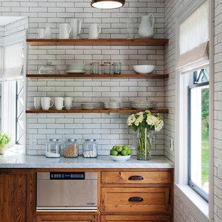 Aménagement d'une cuisine montagne avec un placard avec porte à panneau encastré, des portes de placard en bois brun, un plan de travail en granite, une crédence blanche, une crédence en carrelage métro et un électroménager en acier inoxydable.