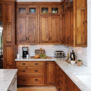 Cette photo montre une cuisine montagne en L avec un évier encastré, un placard avec porte à panneau encastré, des portes de placard en bois brun, un plan de travail en granite, une crédence blanche, une crédence en carrelage métro et un sol en brique.