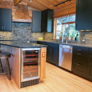 ポートランドの広いラスティックスタイルのおしゃれなキッチン (シェーカースタイル扉のキャビネット、黒いキャビネット、シルバーの調理設備、淡色無垢フローリング、アンダーカウンターシンク、ソープストーンカウンター、マルチカラーのキッチンパネル、石タイルのキッチンパネル、ベージュの床) の写真
