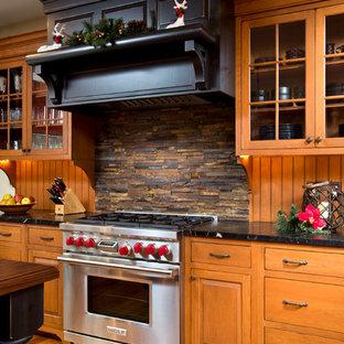 Exemple d'une cuisine chic avec un électroménager en acier inoxydable et une crédence en ardoise.