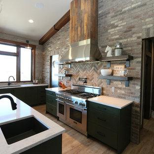 他の地域のエクレクティックスタイルのおしゃれなキッチン (ダブルシンク、フラットパネル扉のキャビネット、緑のキャビネット、人工大理石カウンター、グレーのキッチンパネル、レンガのキッチンパネル、シルバーの調理設備の、クッションフロア) の写真