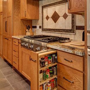 ソルトレイクシティの広いサンタフェスタイルのおしゃれなキッチン (シェーカースタイル扉のキャビネット、中間色木目調キャビネット、御影石カウンター、磁器タイルの床、マルチカラーのキッチンパネル、磁器タイルのキッチンパネル、シルバーの調理設備、アンダーカウンターシンク、グレーの床) の写真
